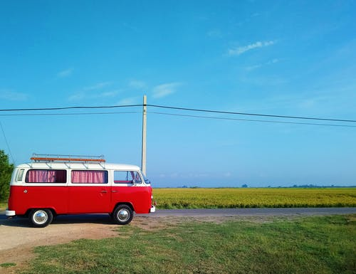 Red and White Volkswagen T-2 on Green Grass Field
