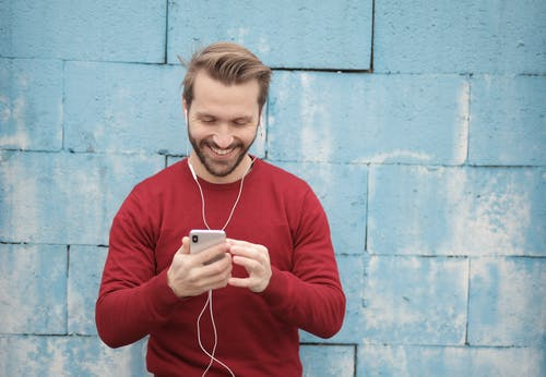 Cheerful young man listening to music in earphones on smartphone on street near wall