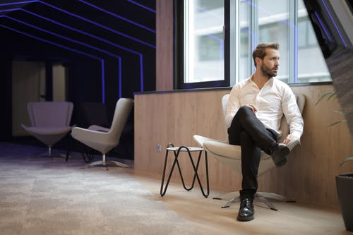 Confident businessman sitting on armchair near window in modern spacious workspace