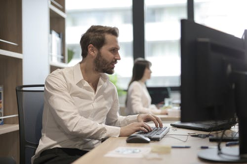 Thoughtful young bearded manager typing on keyboard while working on computer in modern office