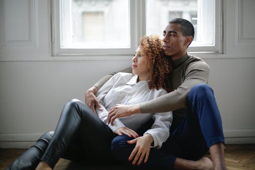 Thoughtful young ethnic couple hugging while sitting on floor near window