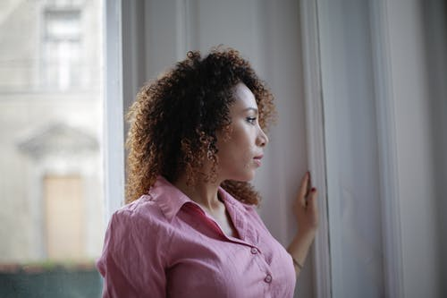 Pensive young ethnic lady looking through window at home