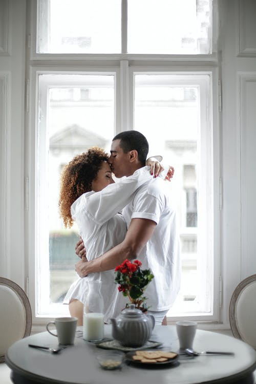 Couple Hugging And Kissing While Standing Near Window At Home