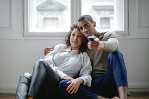 Loving ethnic couple watching movie embracing on floor near window