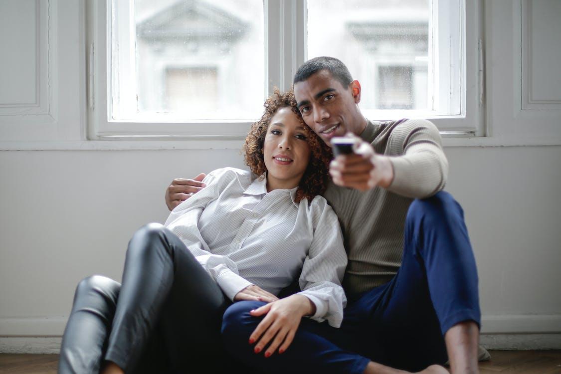 Loving ethnic couple watching movie embracing on floor near window
