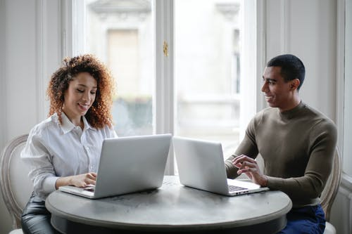 Cheerful young couple using laptops while sitting at table near window at home
