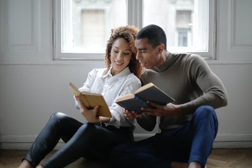 Positive young ethnic couple reading books while sitting on floor near window