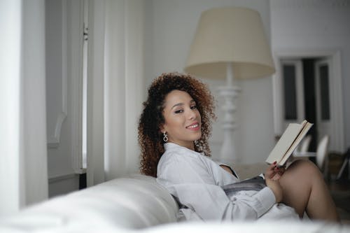 Woman in White Long Sleeve Shirt Sitting on Couch Holding a Book