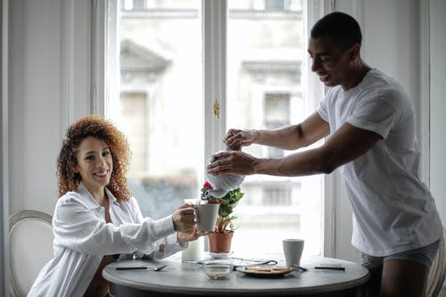 Man in White Shirt Pouring Hot Water on Woman's Cup