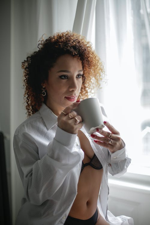 Woman in White Dress Shirt Holding White Ceramic Mug