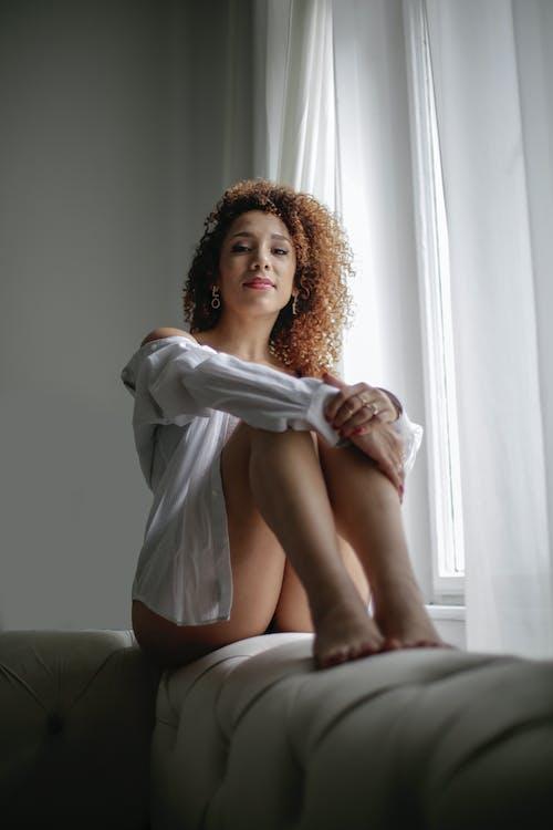 Woman in White Long Sleeve Shirt Sitting Near the Window
