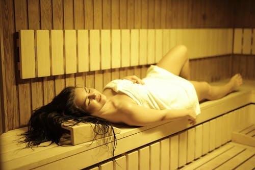 Woman Lying Down in Sauna Room