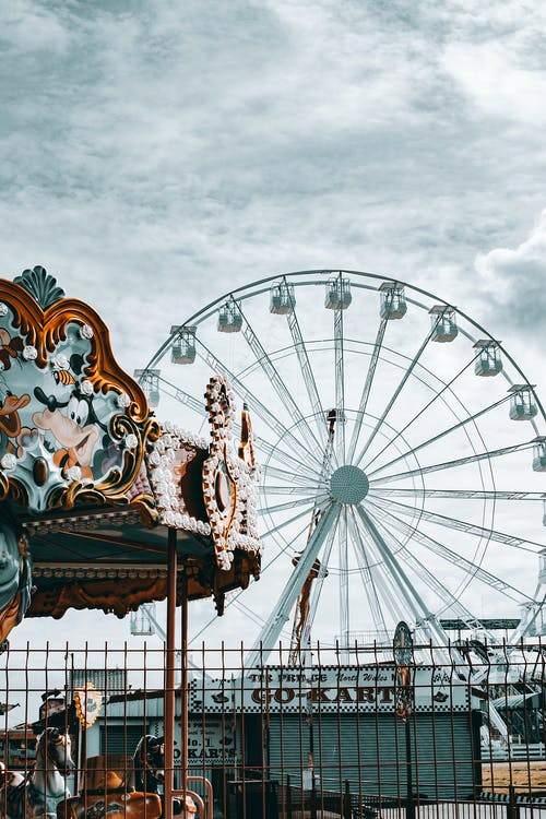 Ferris Wheel and Carousel Under White Clouds and Blue Sky