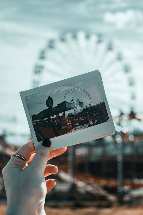 Person Holding Photo of Amusement Park