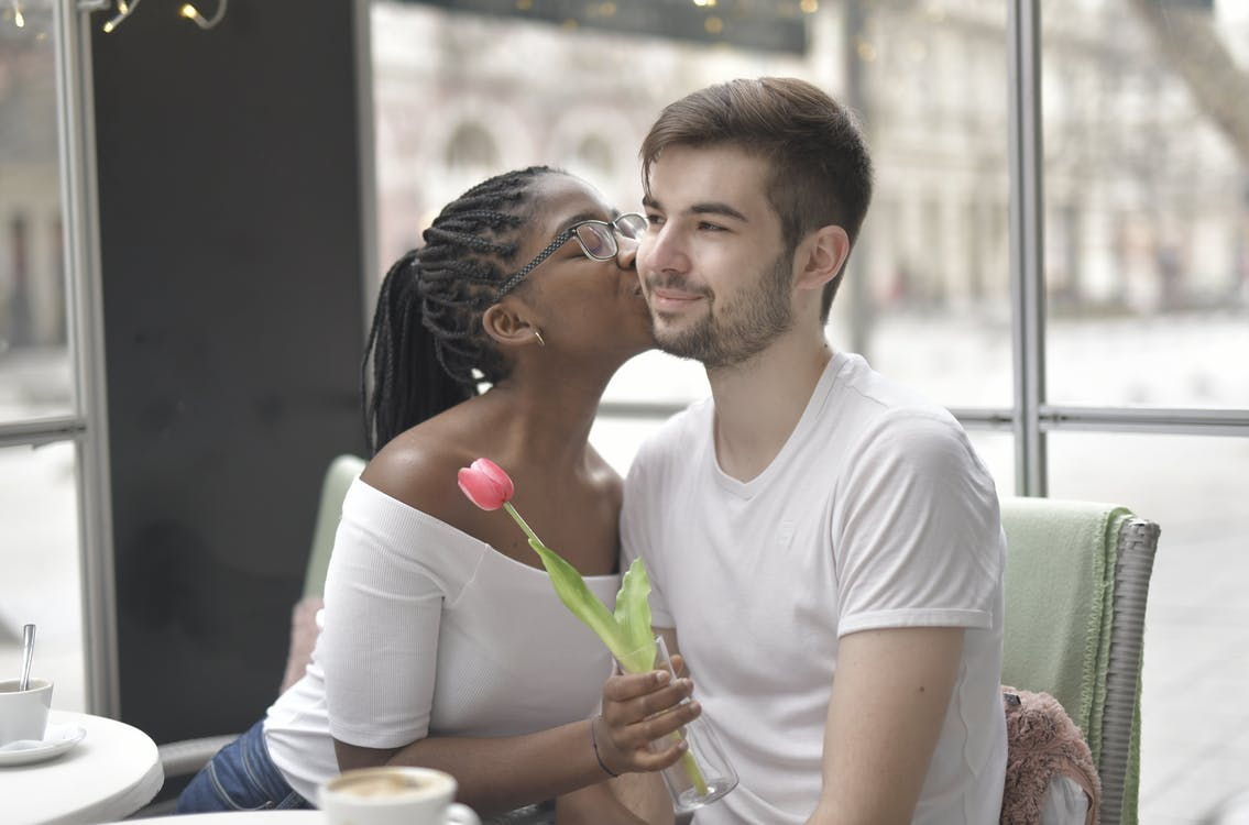 Woman Holding a Flower Kissing a Man