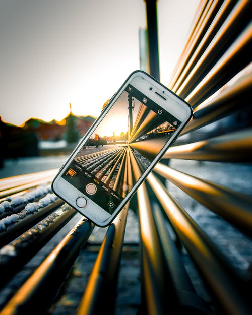 Silver Iphone 6 on Train Rail during Sunset