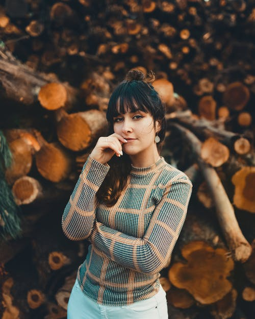 Beautiful Woman Standing In Front of Log Pile