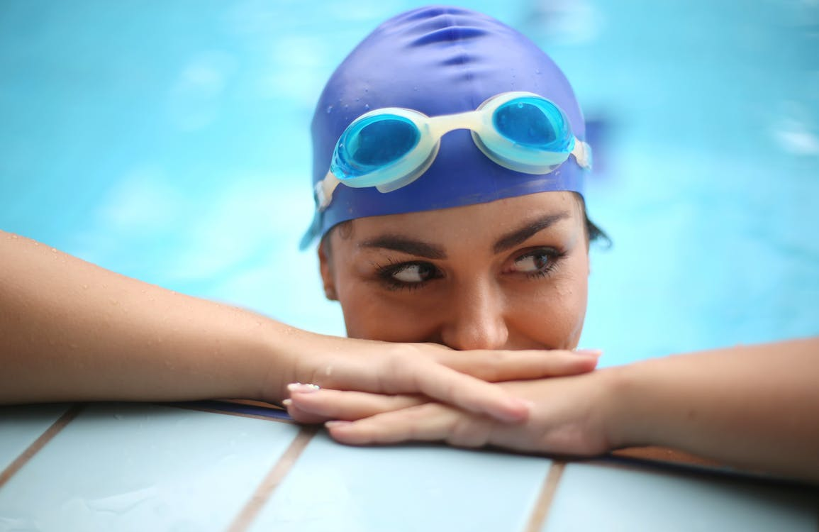 Person Wearing Blue Goggles and Swimming Cap