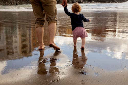 Father and Child Walking on the Shore