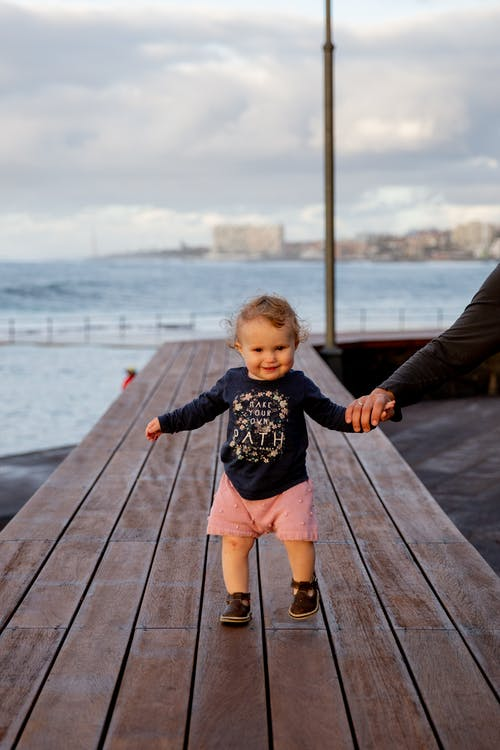 Little Girl Walking on Wooden Dock