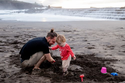 Father and Child Playing on Black Sand