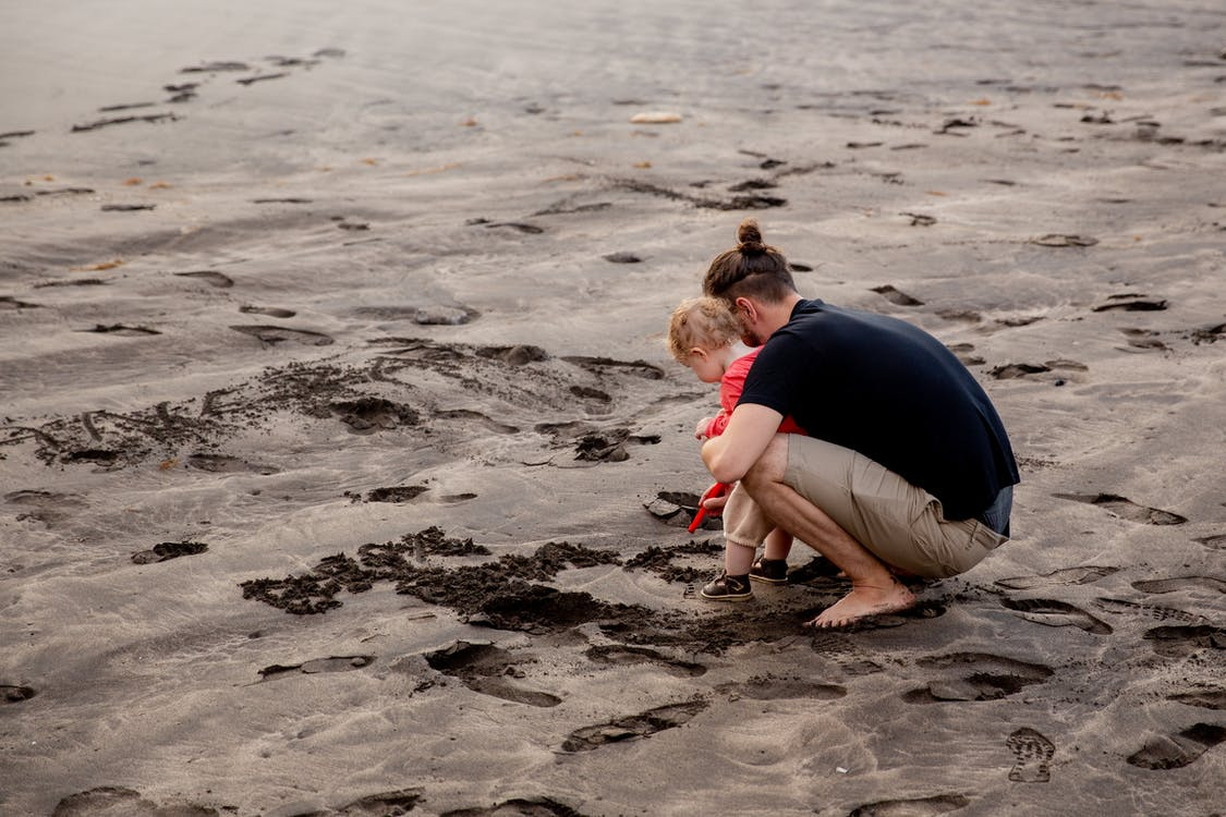 Father and Child Playing on Sand