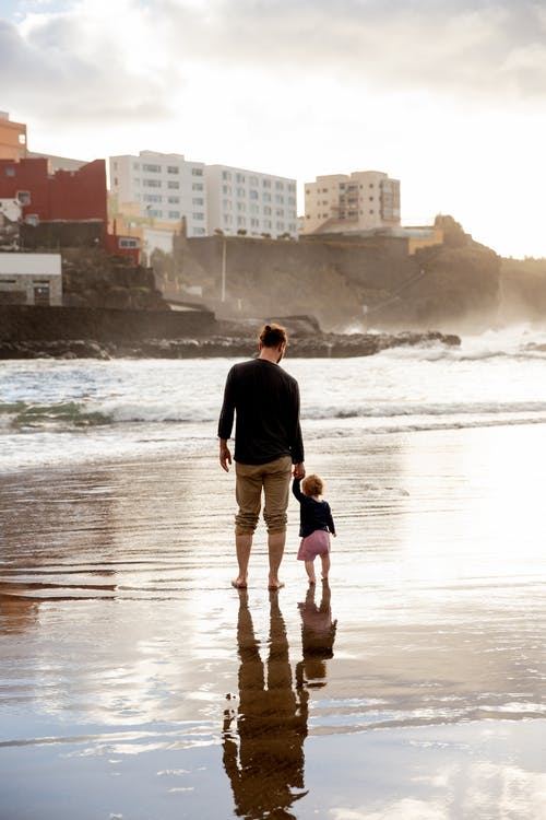 Father and Child Walking on Shore