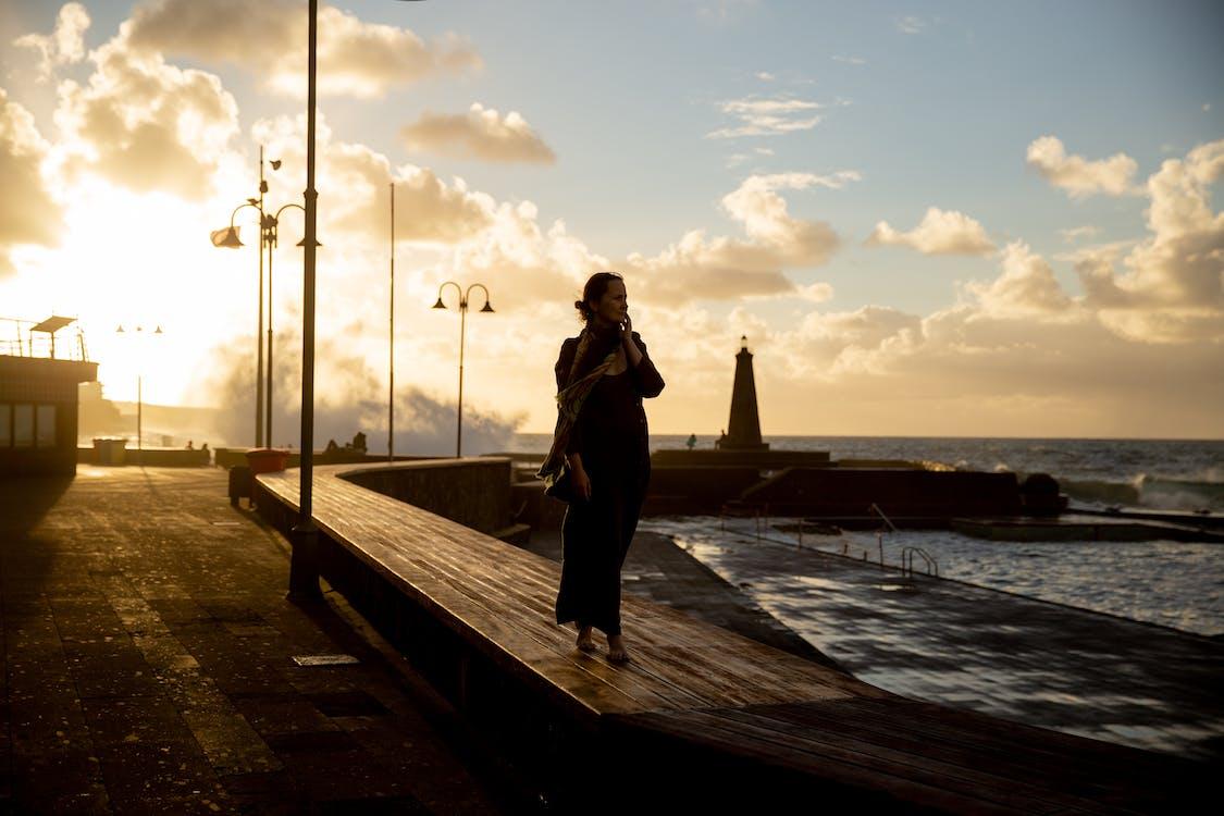 Woman Walking on Wooden Dock at Sundown