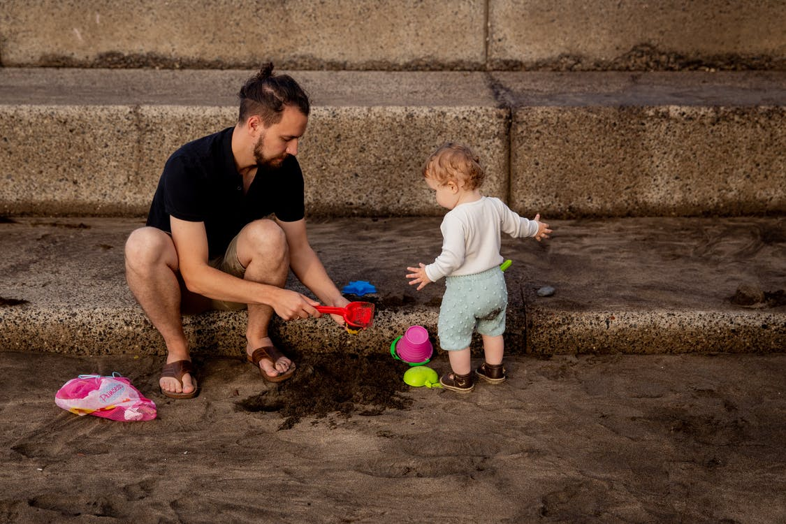Father and Child Playing With Sand