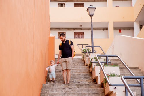 Man and Child Walking Down on Stairs
