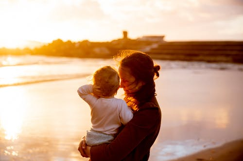 Woman Carrying Baby in White Shirt Watching the Sunset