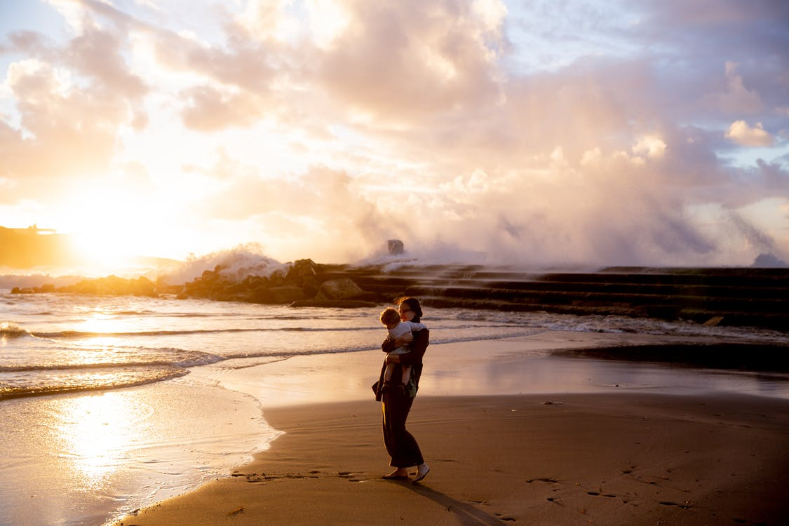 Woman Standing on Seashore Carrying Her Child during Sunset