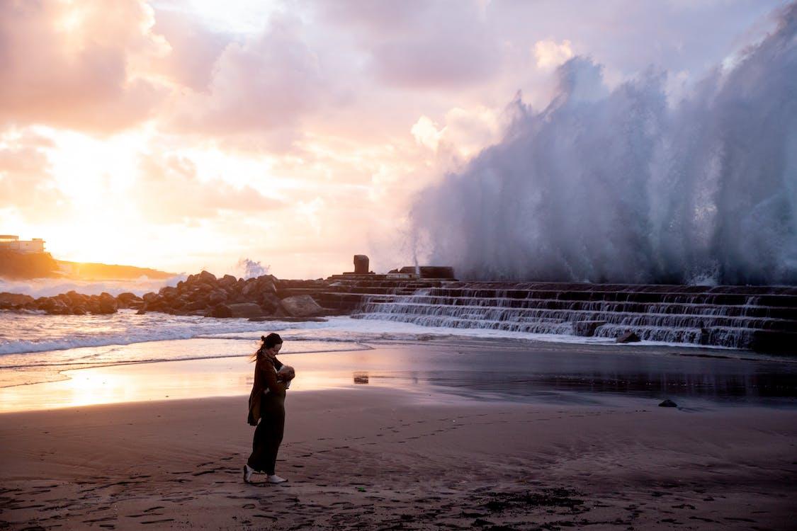 Woman in Black Dress Standing on Seashore