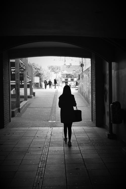 Woman with bag walking in dark passage