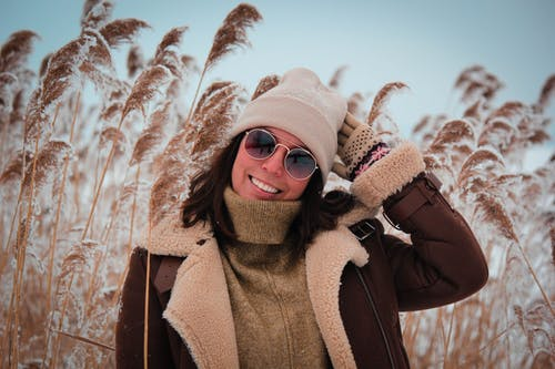 Woman in Brown Coat Wearing Brown Beanie and Brown Sunglasses