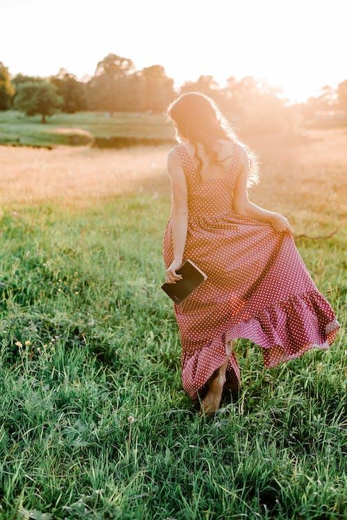 Woman in Polka Dot Dress Standing on Green Grass Field