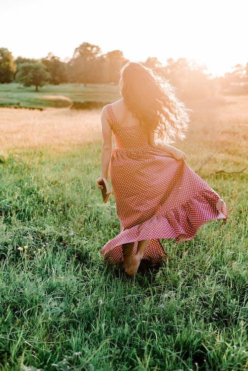 Woman in Polka Dot Dress Walking on Green Grass Field