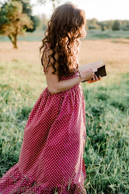 Girl in Red and White Polka Dots Dress Holding Book