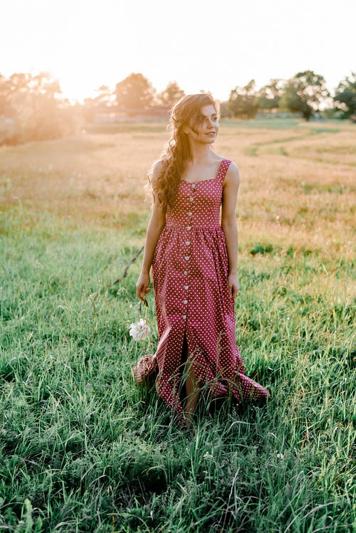 Woman in Red and White Polka Dots Dress Standing on Green Grass Field