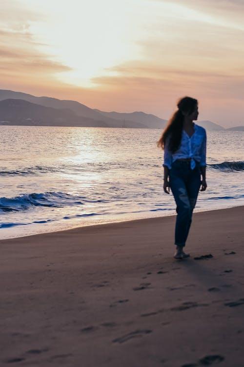 Woman In Blue Denim Jeans Standing On Beach