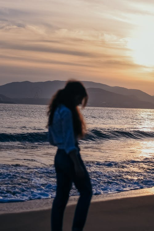 Woman Standing on Seashore during Sunset