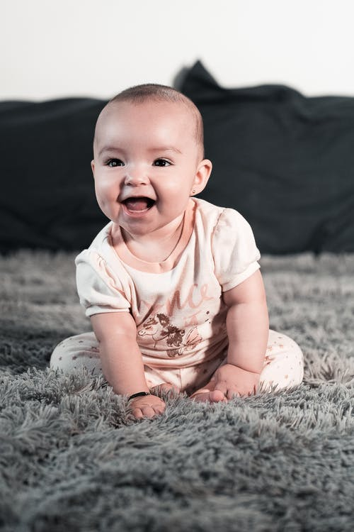 Baby in White Shirt Lying on Gray Textile