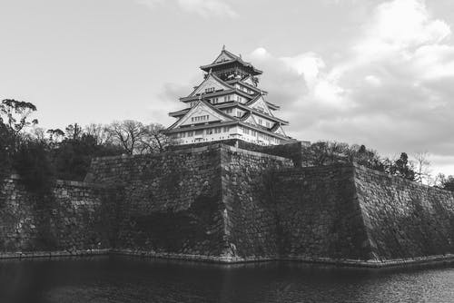 Grayscale Photo of Osaka Castle Near Body of Water