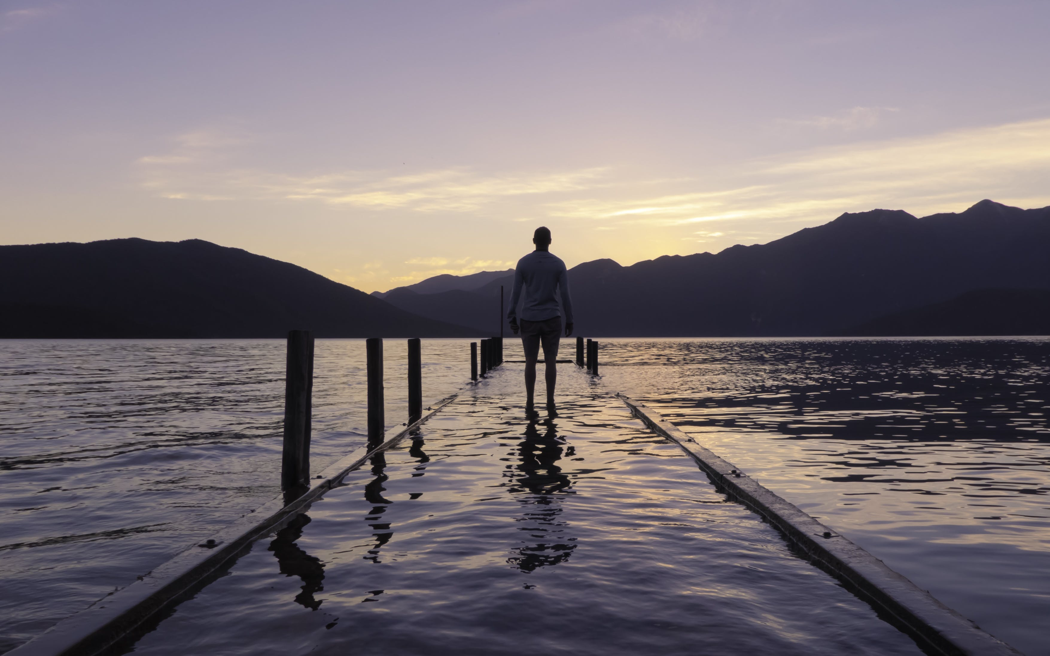 Person Standing on Dock With Water