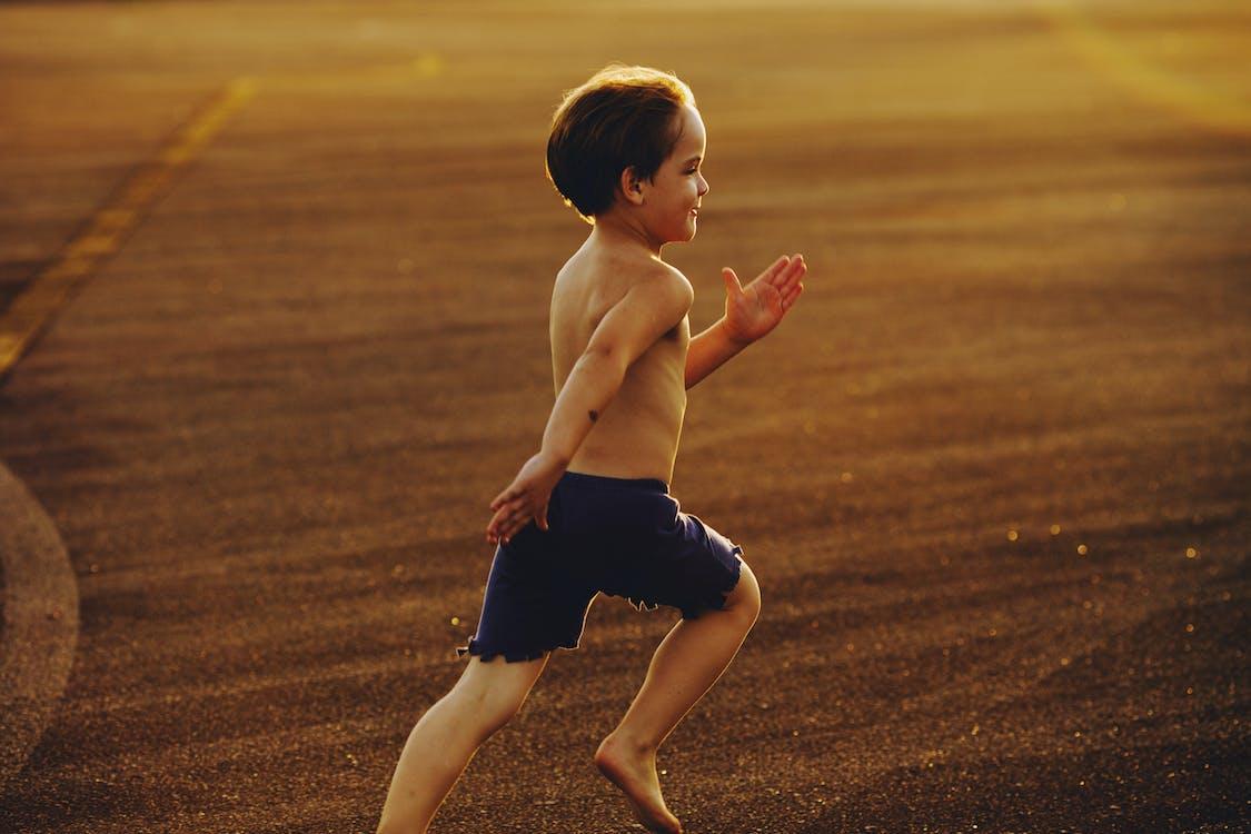 Topless Boy In Schwarzen Shorts Läuft Auf Brown Field