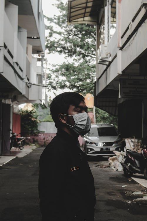 Man Wearing Face Mask Standing Near White Car