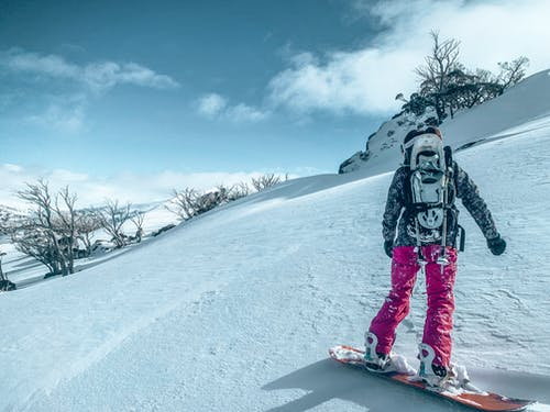Person in Black Jacket and Pink Pants Standing on Snow Covered Ground Snowboarding