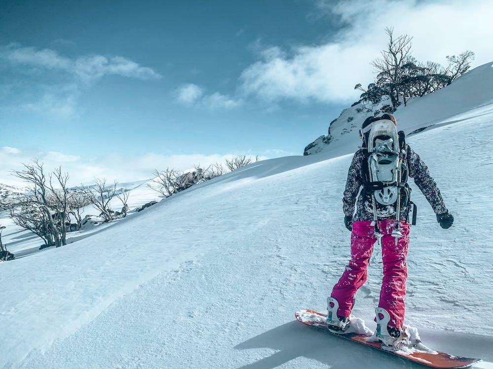 Person In Der Schwarzen Jacke Und In Der Rosa Hose, Die Auf Dem Schneebedeckten Boden Snowboarding Stehen