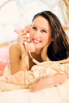 Smiling Woman Talking over the Corded Telephone