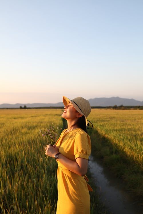 Woman in Brown Sun Hat and Yellow Dress Standing on Green Grass Field
